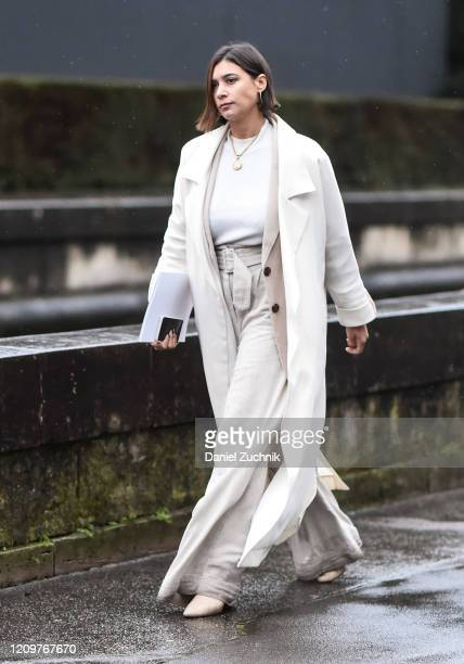 Guest is seen wearing a white coat, white top, beige pants and beige belt outside the Valentino show during Paris Fashion Week: AW20 on March 01,...