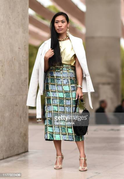 Guest is seen wearing a white jacket, gold Paco Rabanne top and green and gold skirt with gold heels outside the Paco Rabanne show during Paris...