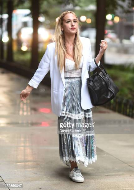 Guest is seen wearing a white jacket, white blouse and silver skirt with black bag outside the Rag & Bone show during New York Fashion Week S/S20 on...