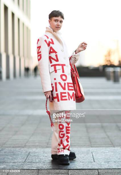 A guest is seen wearing a white Official Rebrand outfit with bag outside the Tanaka show during New York Fashion Week Men's Fall/Winter 2019 on...