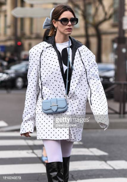 A guest is seen wearing a white polka dot jacket and Prada purse outside the Miu Miu show during Paris Fashion Week AW20 on March 03 2020 in Paris...