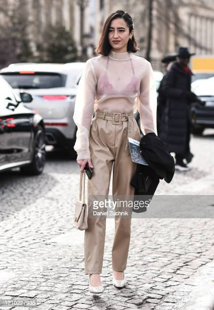 Guest is seen wearing a white sheer top, pink bra and beige pants outside the Chanel show during Paris Fashion Week: AW20 on March 03, 2020 in Paris,...