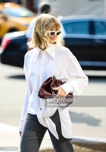 A guest is seen wearing a white shirt and black and white pants during New York Fashion Week on September 11 2019 in New York City