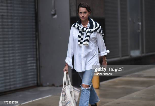 A guest is seen wearing a white shirt striped sweater and blue jeans outside the Rag Bone show during New York Fashion Week S/S20 on September 06...