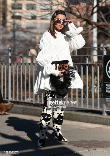 A guest is seen wearing a white top and black and white pants with an animal print fur purse outside the Son Jung Wan show during New York Fashion...