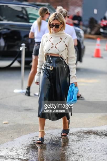 Guest is seen wearing a white top and black skirt during New York Fashion Week on September 11, 2019 in New York City.
