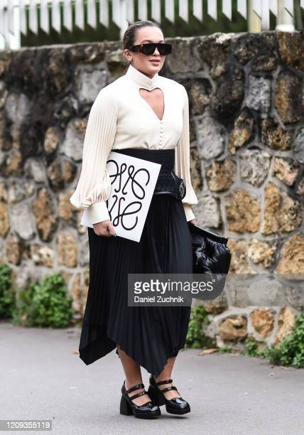 Guest is seen wearing a white top and Loewe black skirt outside the Loewe show during Paris Fashion Week: AW20 on February 28, 2020 in Paris, France.