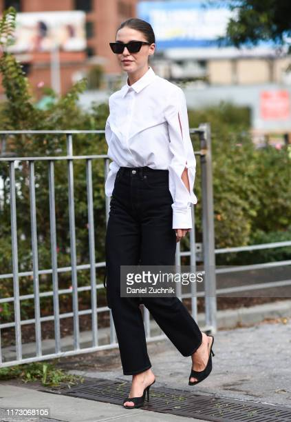 A guest is seen wearing a white top black pants and black heels outside the Area show during New York Fashion Week S/S20 on September 07 2019 in New...