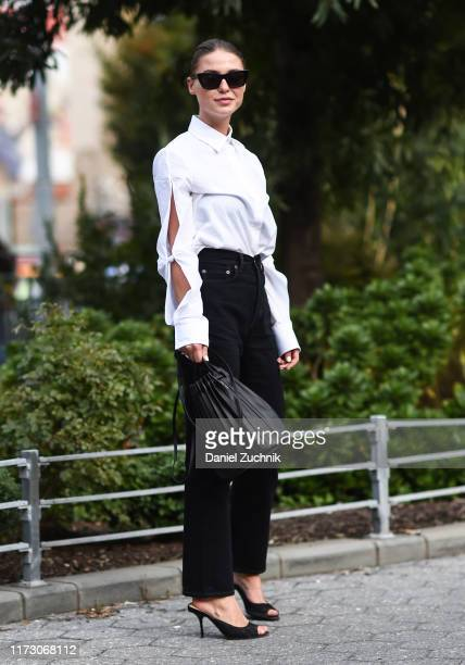 A guest is seen wearing a white top black pants black leather bag and black heels outside the Area show during New York Fashion Week S/S20 on...