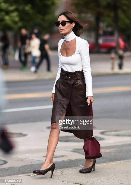 A guest is seen wearing a white top maroon leather skirt and bag outside the Area show during New York Fashion Week S/S20 on September 07 2019 in New...