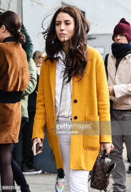 A guest is seen wearing a yellow cardigan with Louis Vuitton bag outside of the 31 Phillip Lim show during New York Fashion Week Women's Fall/Winter...