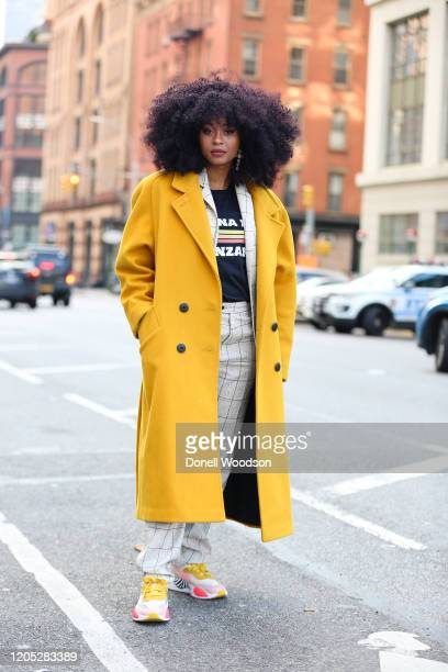 Guest is seen wearing a yellow coat and white suit outside of Spring Studios during New York Fashion Week on February 09, 2020 in New York City.