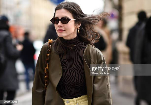 Guest is seen wearing an Altuzarra green coat and black sheer top outside the Altuzarra show during Paris Fashion Week: AW20 on February 29, 2020 in...