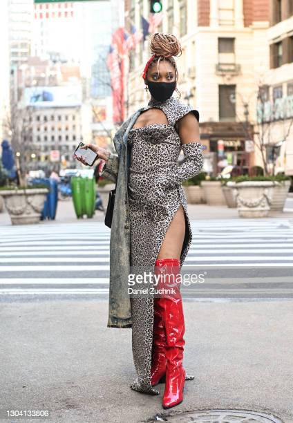Guest is seen wearing an animal print dress and red boots outside the Christian Siriano show during New York Fashion Week F/W21 on February 25, 2021...