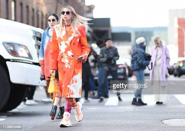 A guest is seen wearing an orange and white print coat and sneakers outside the Sies Marjan show during New York Fashion Week Fall/Winter 2019 on...