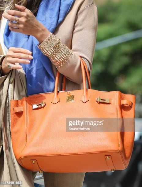A guest is seen wearing an orange Hermès purse in front of Spring Studios during New York Fashion Week on September 09 2019 in New York City