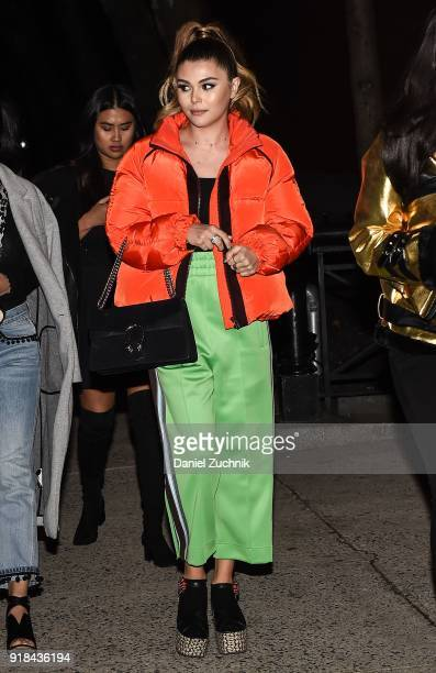 A guest is seen wearing an orange puff coat and green striped pants outside the Marc Jacobs show during New York Fashion Week Women's A/W 2018 on...