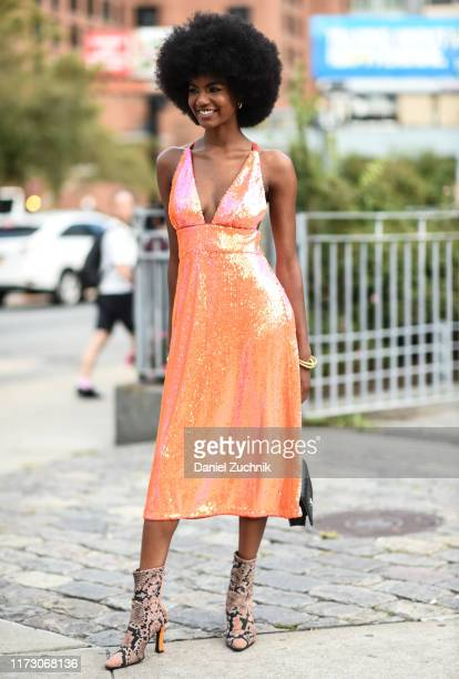 A guest is seen wearing an orange shiny dress and animal print boots outside the Area show during New York Fashion Week S/S20 on September 07 2019 in...