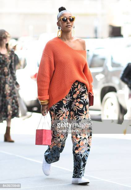 A guest is seen wearing an orange sweater and floral pants outside the Noon by Noor show during New York Fashion Week Women's S/S 2018 at Skylight...