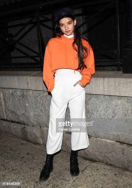 A guest is seen wearing an orange top and white pants with black shoes outside the Marc Jacobs show during New York Fashion Week Women's A/W 2018 on...