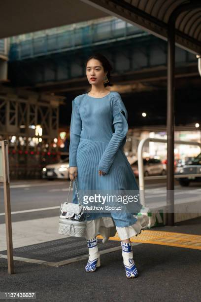A guest is seen wearing baby blue dress with pleated skirt white skirt layered blue/white shoes and Chanel silver bag during the Amazon Fashion Week...