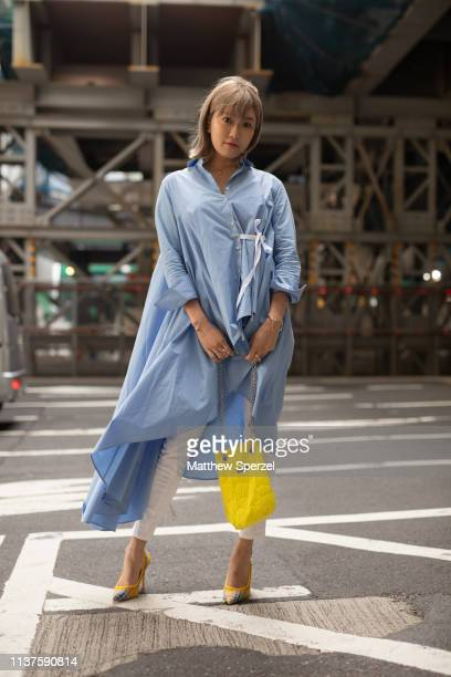 A guest is seen wearing baby blue dress yellow bag and white pants during the Amazon Fashion Week TOKYO 2019 A/W on March 22 2019 in Tokyo Japan