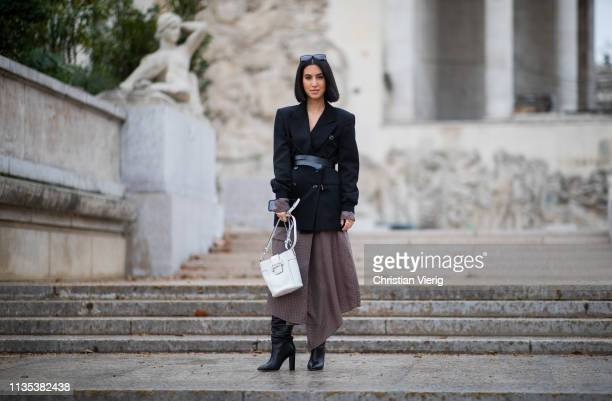 A guest is seen wearing bag asymmetric skirt black blazer with belt outside Tods lunch during Paris Fashion Week Womenswear Fall/Winter 2019/2020 on...