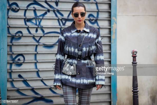 Guest is seen wearing bag, jacket with print, checkered pants outside Paco Rabanne during Paris Fashion Week - Womenswear Spring Summer 2021 : Day...