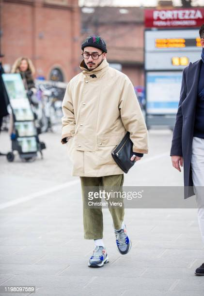 A guest is seen wearing beanie beige jacket khaki pants black clutch during Pitti Uomo 97 at Fortezza Da Basso on January 07 2020 in Florence Italy