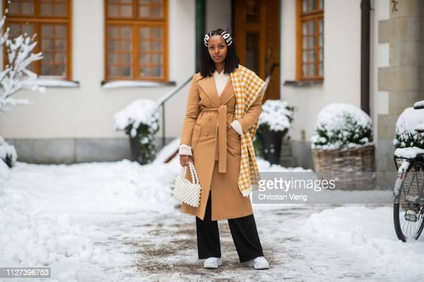 A guest is seen wearing beige belted wool coat plaid scarf Dior hair clip black wide leg pants during Stockholm Runway Autumn Winter 2019 on February...