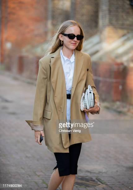 Guest is seen wearing beige blazer, cropped pants, white bag outside Rocha during London Fashion Week September 2019 on September 15, 2019 in London,...