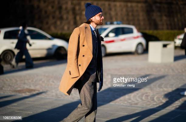 A guest is seen wearing beige coat beanie during the 95th Pitti Uomo at Fortezza Da Basso on January 10 2019 in Florence Italy