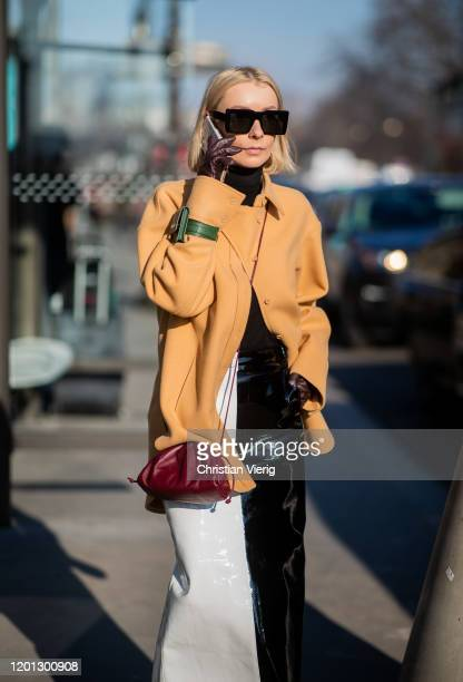 A guest is seen wearing beige coat black white two tone coat green Jacquemus bag around her arm outside Elie Saab during Paris Fashion Week Haute...