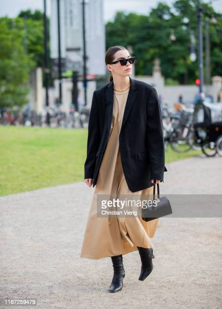Guest is seen wearing beige dress, black blazer outside Samsøe & Samsøe during Copenhagen Fashion Week Spring/Summer 2020 on August 07, 2019 in...