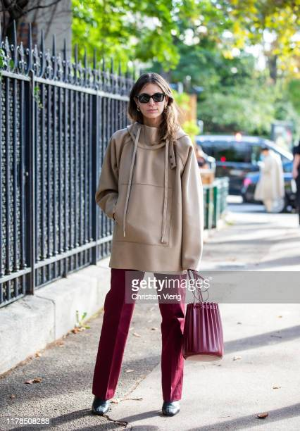 A guest is seen wearing beige jumper bordeaux bag and pants outside Lacoste during Paris Fashion Week Womenswear Spring Summer 2020 on October 01...