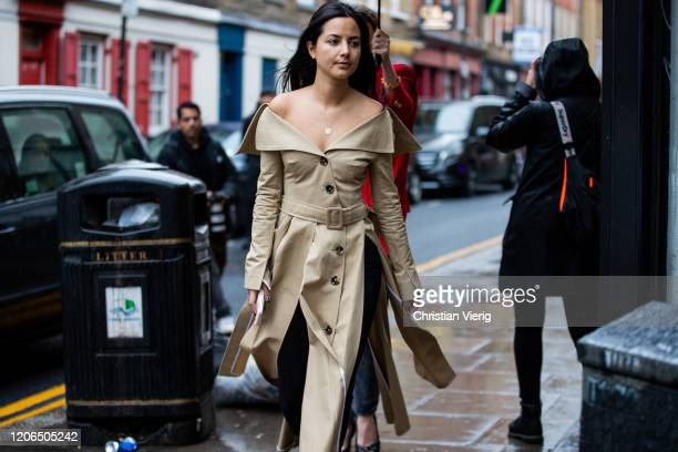 A guest is seen wearing beige off shoulder trench coat outside Marques Almeida during London Fashion Week February 2020 on February 15 2020 in London...