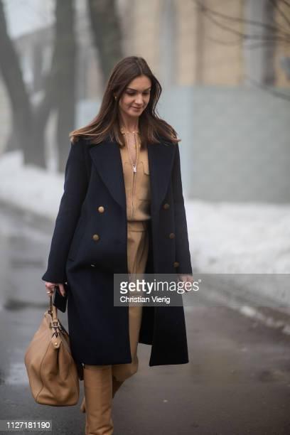 Guest is seen wearing beige pants, top, navy double breasted coat, beige bag during the Ukrainian Fashion Week 2019/20 on February 03, 2019 in Kiev,...