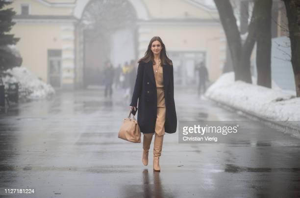 A guest is seen wearing beige pants top navy double breasted coat beige bag during the Ukrainian Fashion Week 2019/20 on February 03 2019 in Kiev...