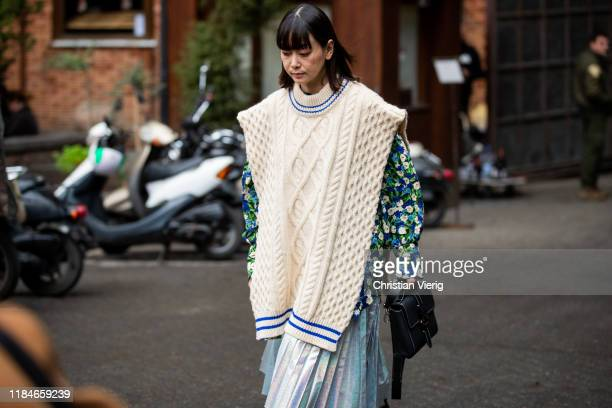 A guest is seen wearing beige slipover jacket with floral print pleated skirt black bag during day 1 of the MercedesBenz Tbilisi Fashion Week on...