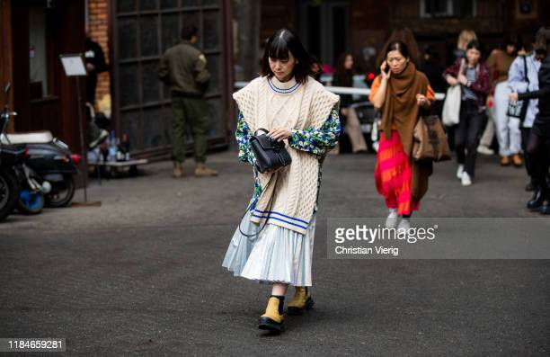 A guest is seen wearing beige slipover jacket with floral print pleated skirt black bag boots during day 1 of the MercedesBenz Tbilisi Fashion Week...