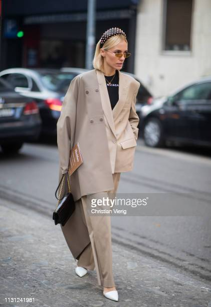 A guest is seen wearing beige suit hair loop outside Max Mara on Day 2 Milan Fashion Week Autumn/Winter 2019/20 on February 21 2019 in Milan Italy