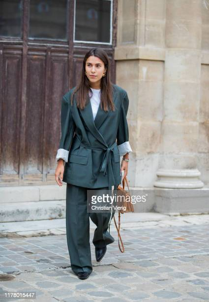 A guest is seen wearing belted green oversized blazer and pants outside Thom Browne during Paris Fashion Week Womenswear Spring Summer 2020 on...
