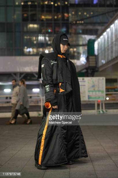 A guest is seen wearing black and orange coat and pants black hoodie and cap during the Amazon Fashion Week TOKYO 2019 A/W on March 23 2019 in Tokyo...