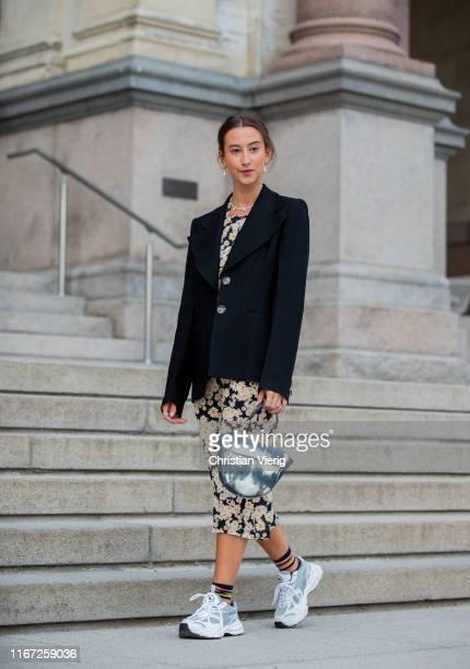 A guest is seen wearing black blazer dress with floral print sneaker two tone bag outside Samsøe Samsøe during Copenhagen Fashion Week Spring/Summer...