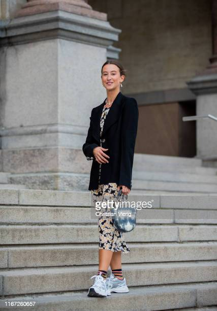 A guest is seen wearing black blazer dress with floral print sneaker two tone bag outside Samsøe Samsøe during Copenhagen Fashion Week Spring/Summer...