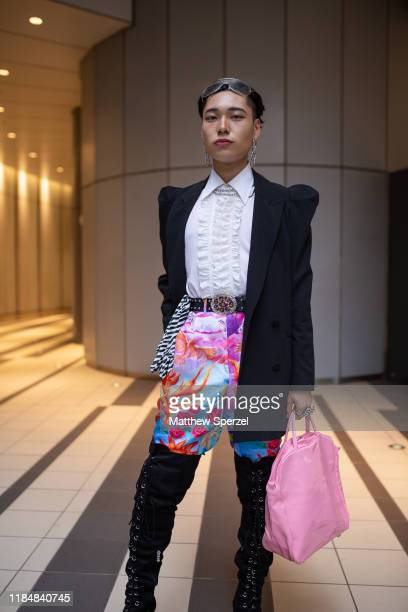 Guest is seen wearing black blazer, white collared shirt, colorful print pants, knee-high boots, pink bag during the Rakuten Fashion Week TOKYO 2020...
