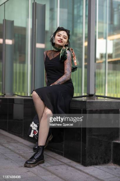 A guest is seen wearing black boots cat bag black dress reptile skin pattern shirt green scarf during the Amazon Fashion Week TOKYO 2019 A/W on March...