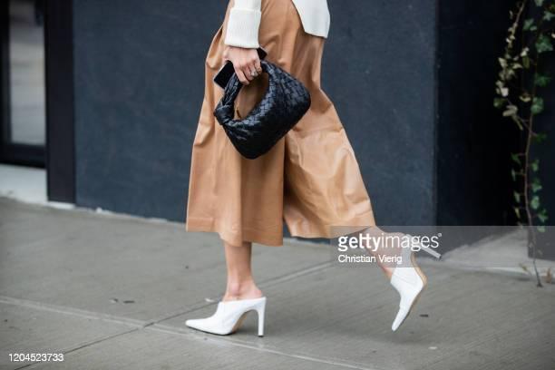 A guest is seen wearing black Bottega Veneta bag beige cropped pants outside Tadashi Shoji during New York Fashion Week February 2020 on February 06...