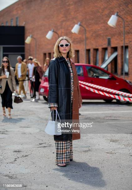 A guest is seen wearing black brown two tone leather coat plaid pants outside By Malene Birger during Copenhagen Fashion Week Spring/Summer 2020 on...