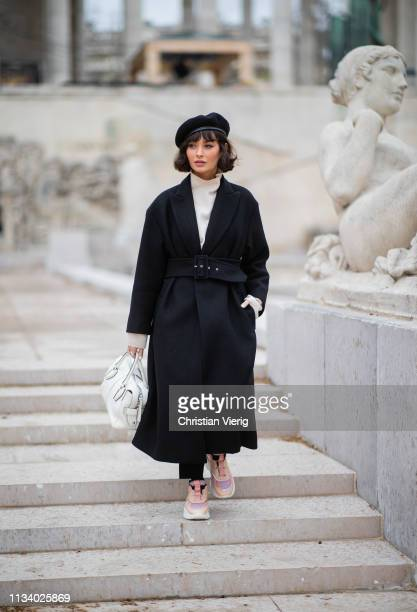 A guest is seen wearing black coat beret bag outside Tods lunch during Paris Fashion Week Womenswear Fall/Winter 2019/2020 on March 05 2019 in Paris...